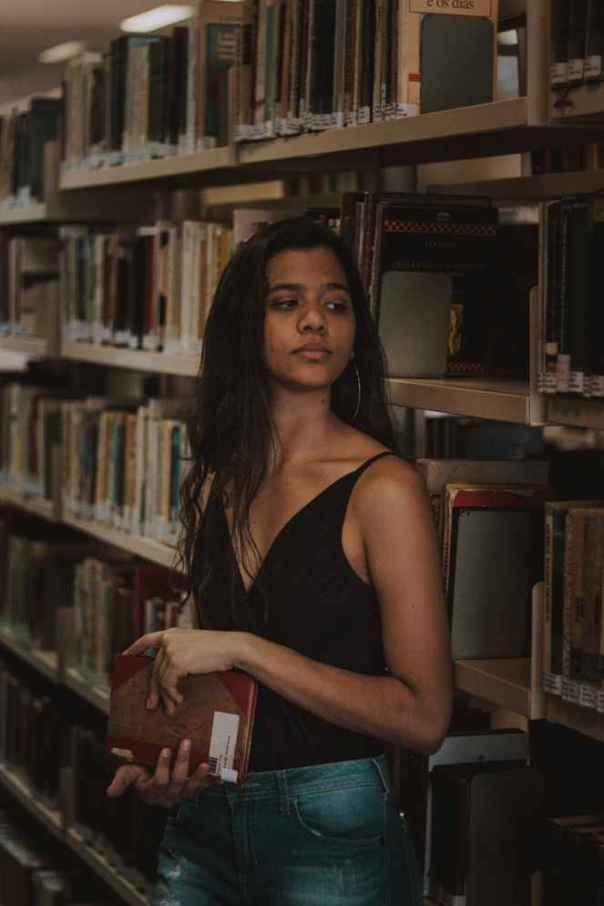 woman in black top holding a book