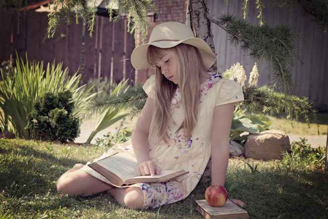 girl in white and blue dress reading books while sitting on lawn