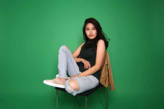 woman wearing black sleeveless top and distressed blue denim jeans outfit while sitting on chair