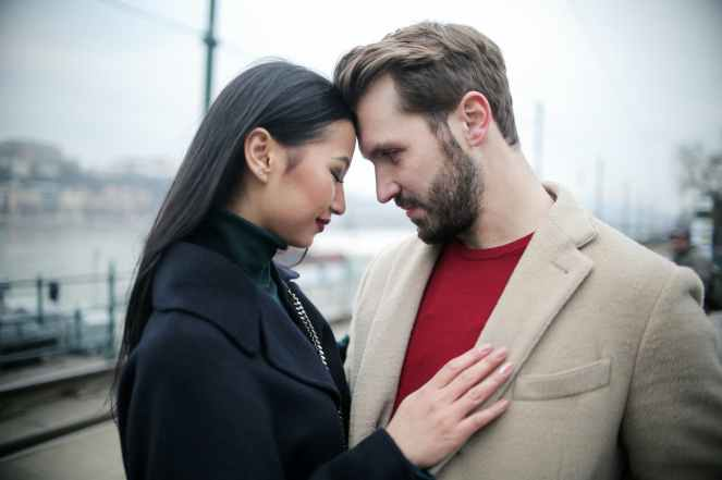 happy multiracial couple hugging on waterfront while having romantic date in city